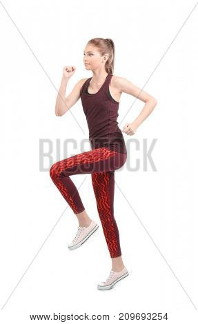 Young sporty woman running on white background