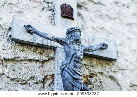 Dirty antique statue of Holy cross with crucified Jesus Christ religion faith death resurrection eternity concept)