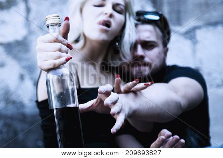 Couple sitting on the table and drinking alcohol. Drunk young people (alcoholism in family pain pity hopelessness social problem of dependence depression concept)