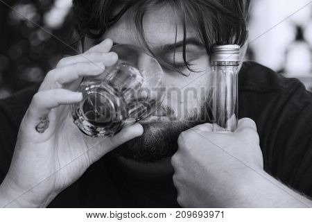 Young male with alcoholic drink looking very sad and depressed. Drunk young people (alcoholism pain pity hopelessness social problem of dependence concept)