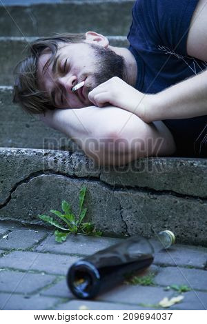 Young male with alcoholic drink smoking and sleeping on the stairs. Drunk young people (alcoholism pain pity hopelessness social problem of dependence concept)