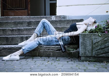 Young female with alcoholic drinksleeping on the stairs outdoors. Drunk young people (alcoholism pain pity hopelessness social problem of dependence concept)