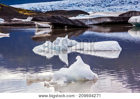 Summer in Iceland. The concept of extreme northern tourism. The cold lake with splinters of ice floes formed by thawed snow of glacier Vatnajokull