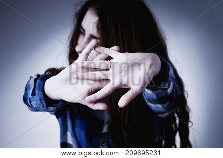Portrait of a young woman looking in fear with her hand in front of face (Gestures body language psychology)