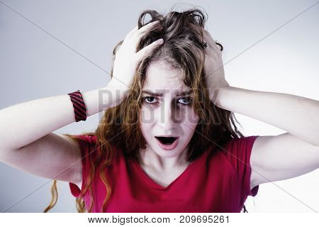 Portrait of a stressed woman holding head in hands (body language gestures psychological portrait)