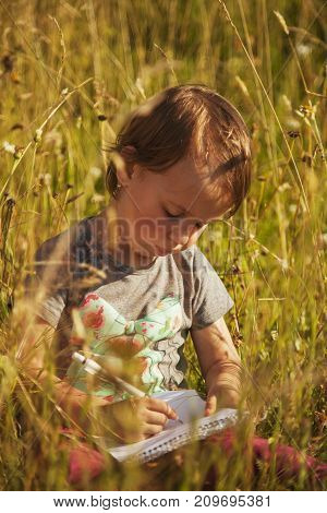 Little beautiful child girl writing in her book outdoors (Education knowledge work success concept)