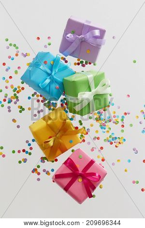 Colorful gift boxes with confetti falling or flying in motion.
