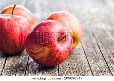 Fresh red apples on old wooden table.