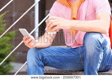 Man with smartphone and cup of coffee sitting on stairs outdoors