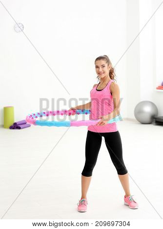 Woman doing exercise with hula hoop in gym