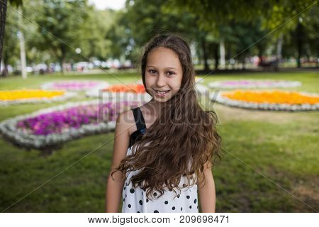 Modern teenage lifestyle. Beautiful portrait. Pretty smiling young girl closeup, focus on foreground. Happy summer style, teenager natural beauty