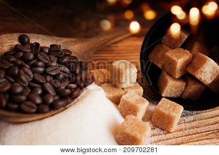 Coffee beans and brown sugar on a wooden table with golden bokeh
