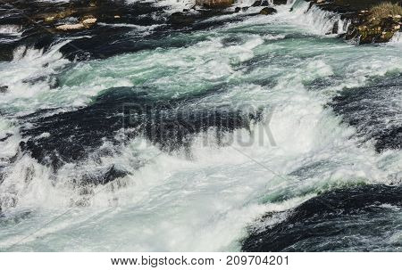 Water of the Rhine river just below the Rhine Falls in Switzerland. The Rhine Falls is the largest waterfall in Europe, located on the border between the Swiss cantons of Zurich and Schaffhausen.