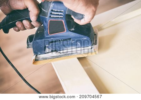 Sanding and preparing old doors with cracked paint for a new lick of paint Smooth sanding or paint removal concept.