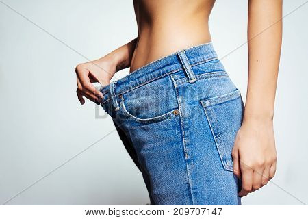 young thin girl shows how thin she is, jeans have become big