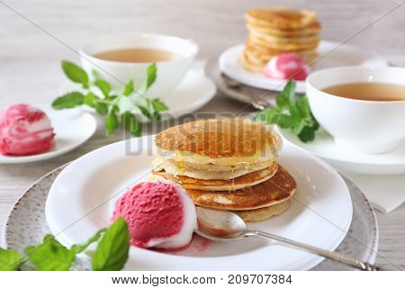 Two portions of banana pancakes with honey and fruit sorbet for breakfast