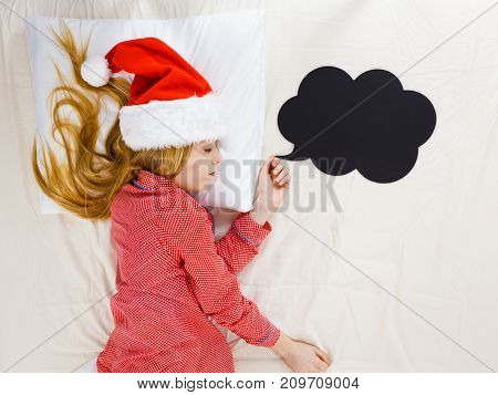 Sleeping woman waiting for Christmas season wearing pajamas and Santa Claus hat lying in bed dreaming about celebrating holiday black speech bubble ballon next to her.