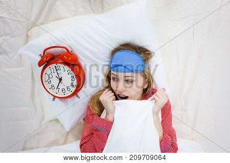 Shocked Woman Wearing Pajamas Holding Clock Overslept