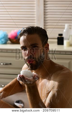 Man With Beard And Seductive Face Blowing Foam From Palm