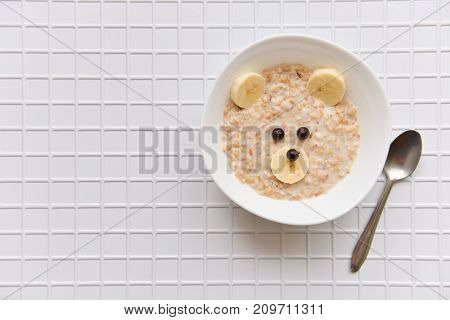 oatmeal porridge with fruit and berries. cheerful children's food with a bear face decoration