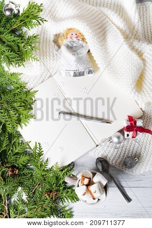 An open notebook on a plaid with a cup of hot cocoa with marshmallow with Christmas tree branches with Christmas decorations and gift box. The concept of a Christmas model flat lay