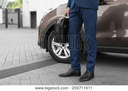 Successful businessman near car outdoors
