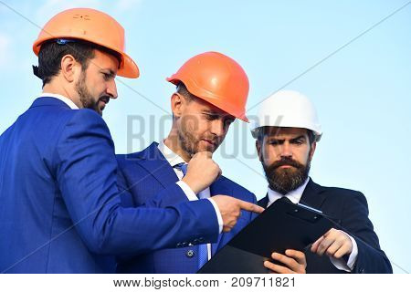 Board of architects with concerned faces in suits and helmets look at tablet. Builders discussing plan outdoors. Coworking and construction concept. Workers and engineer hold meeting on project poster