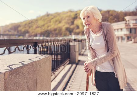 Contemplating landscapes. Charming elderly lady standing on the bridge and looking on the river while heavily leaning on her cane, suffering from a back pain