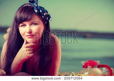 Brunette pin up woman with dotted bow in hair lying on beach sea water in background