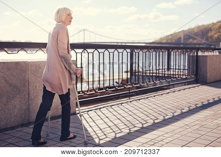 Days of rehabilitation. Pleasant elderly lady walking on crutches along the bridge across the river while being on rehabilitation after trauma
