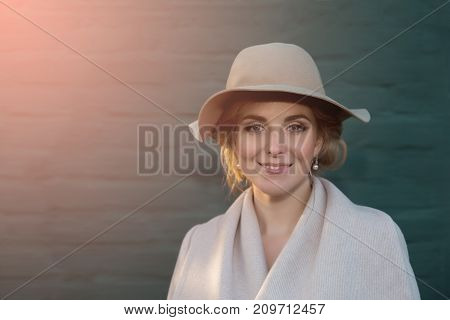 portrait of a beautiful woman in a hat  and coat outdoor . retro wedding style 50-ies. toned photo.