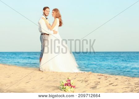 Beautiful bouquet and happy wedding couple on sea beach