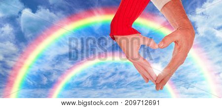 Close up of hands forming heart against view of overcast against blue sky