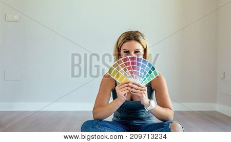 Young woman with color chart sitting in a empty living room