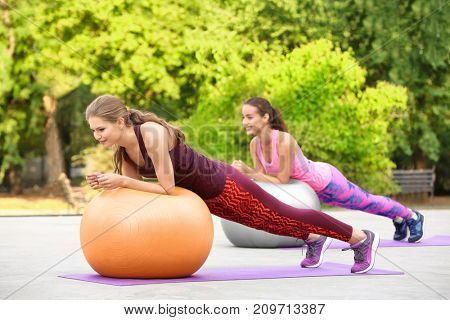 Young women doing exercise with fitness balls on sports ground