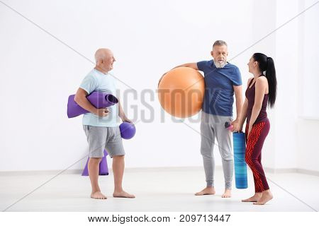 People with yoga mats and fitness ball indoors