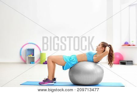Beautiful young woman with fitness ball training in gym