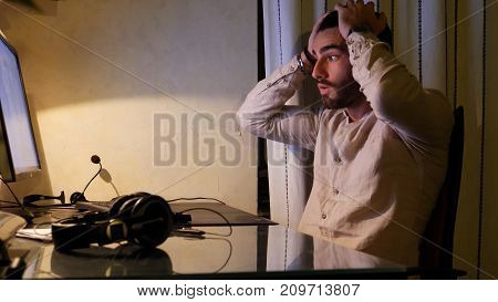 Serious, worried or unhappy attractive young businessman sitting at desk with computer at home, with desperate expression