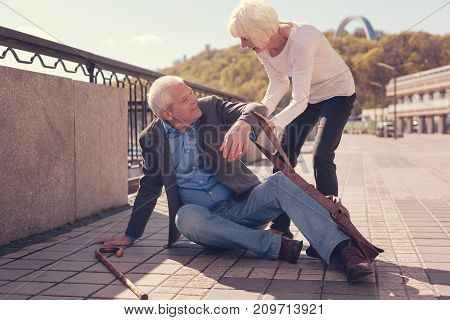Genuine indifference. Polite elderly lady helping a pleasant white-haired senior man get up while he lying on the ground, having fallen down, and looking at her gratefully