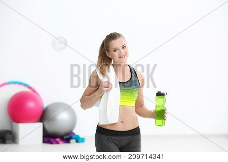 Sporty young woman with bottle of water in gym