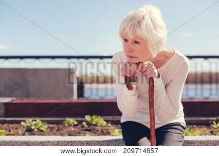 Tormenting thoughts. White-haired elderly lady sitting on the concrete edge of a flower bed, resting her chin on hands folded on a cane and thinking about something disquieting