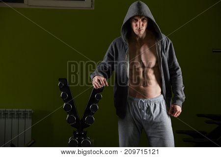 Strong well built bodybuilder lifting dumbbell weights getting ready for exercise in fitness.