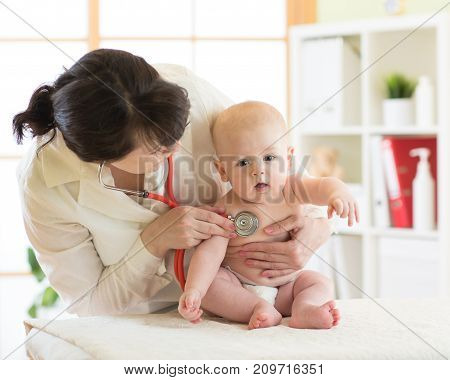 Female doctor pediatrician examining baby boy patient
