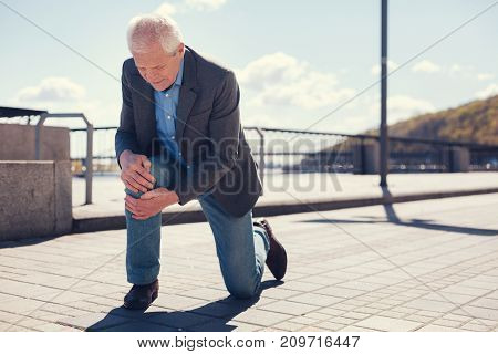 Quick examination. Charming white-haired elderly man standing on one knee and palpating the other one after falling