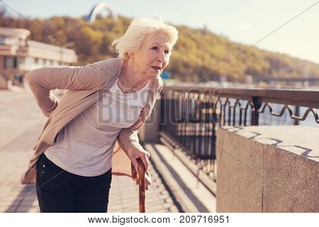 Hard to walk. Thin white-haired senior woman leaning on a cane and touching her sore lower back suffering from pain caused by herniated discs