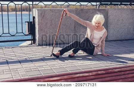 It hurts. Pleasant senior woman leaning on a cane and trying to get up from the pavement after falling down