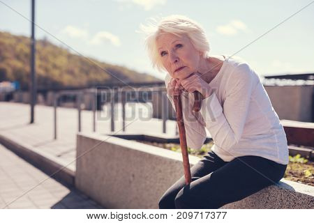 Absorbing loneliness. Beautiful senior lady sitting alone, resting her chin on her hands folded on a cane and looking into the distance wistfully