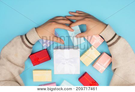 Top view of hands holding a small box with a gift and a ribbon on a blue background.