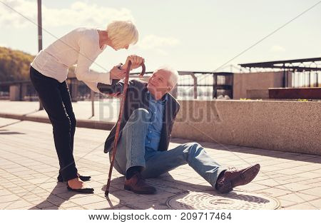 Eager to help. Pleasant senior woman holding the hand of a man sitting on the ground after falling and helping him to get up