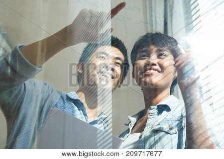 Smiling young Asian developers writing project plan on glass wall